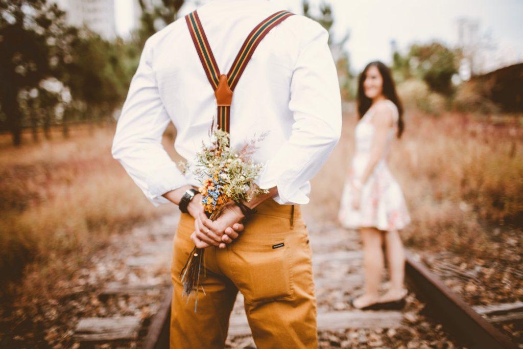 Mann mit Blumenstrauß hinter dem Ruecken ueberrrascht frau