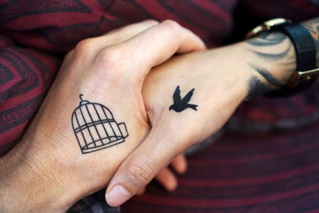 zwei hände mit tattos Käfig und vogel