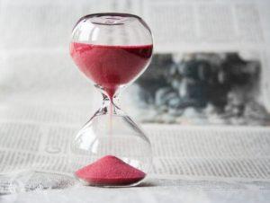 Sanduhr aus Glas mit rosa sand auf Zeitungspapier stehend