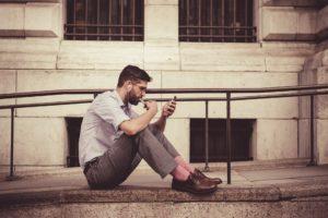 Mann mit Smartphone on Kopfhöhrern auf einer Treppe