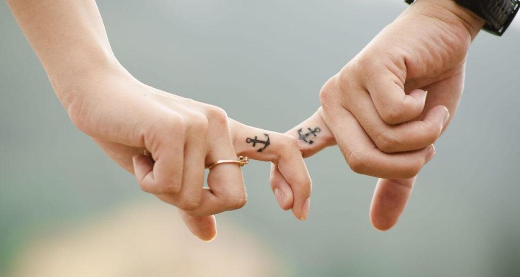 Ein Paar mit einem Ankertattoo, welches Finger hölt