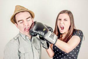 frau mit box handhandschuhen schlägt partner auf wange