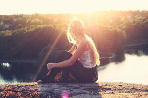 junge blonde frau sittz am Seeufer bei sonntenuntergang