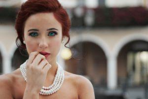 frau mit roten haaren blauen augen und perlenkette